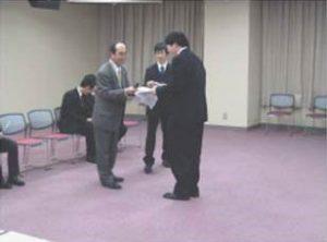 優秀論文賞の表彰状を渡す専攻幹事の安川先生